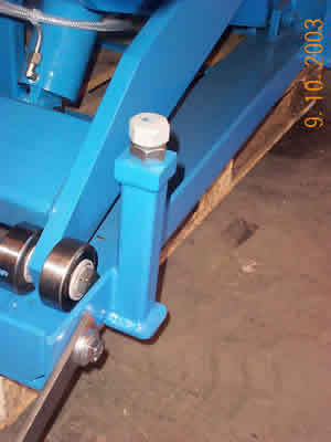 Baseframe of lift table showing adjustable downstops and arm roller bearings