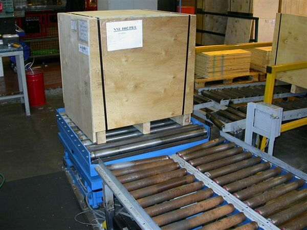 Custom built scissor lift table with rotating gravity roller track on a pallet handling conveyor system